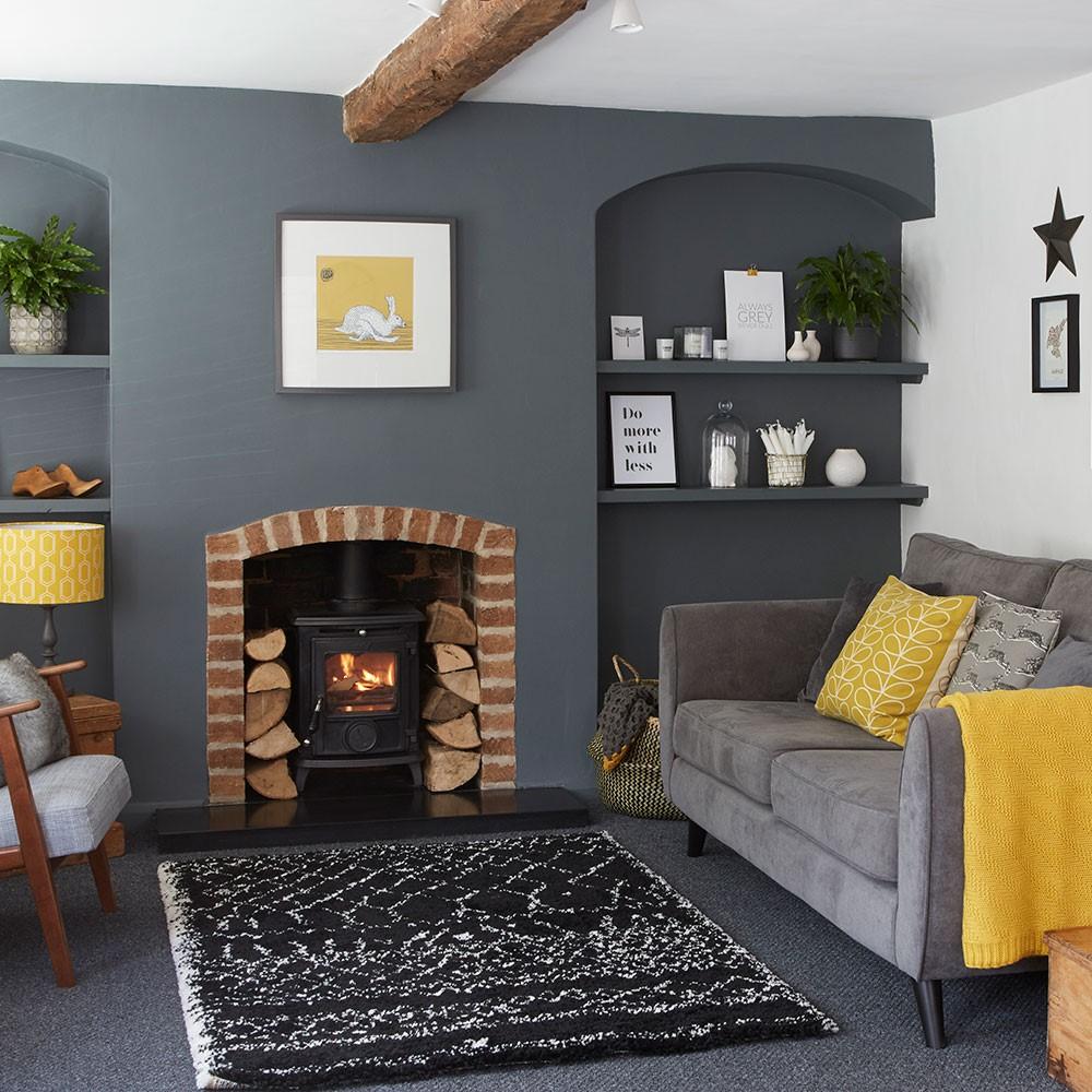 Donkergrijze woonkamer met gele kussens als accent