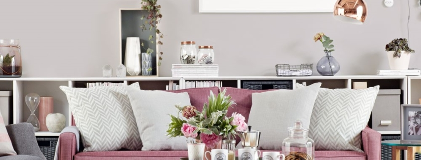 Grijze woonkamer met roze bankstel en koperkleurige accenten
