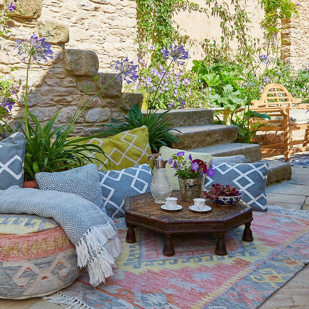 Je terras kleurrijker maken door een kleed te plaatsen en diverse poefs-zitzakken