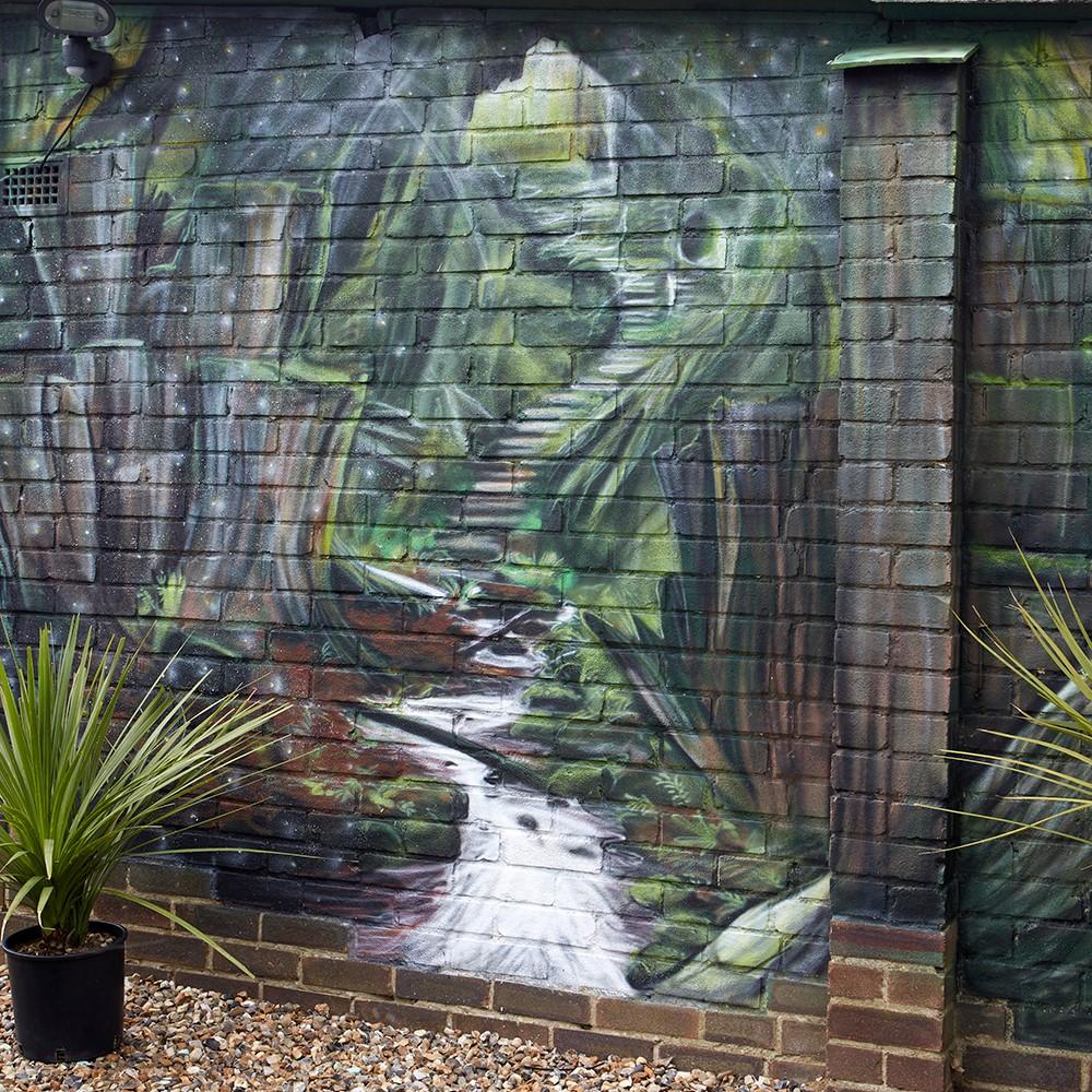 Maak je tuin groter door een muur schildering in een natuurlijke tint te laten uitvoeren
