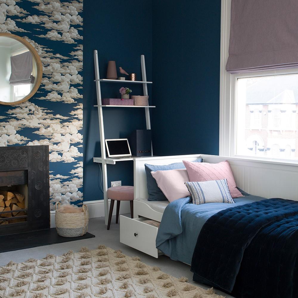 Slaapkamer met donkerblauwe muur en wolkenbehang